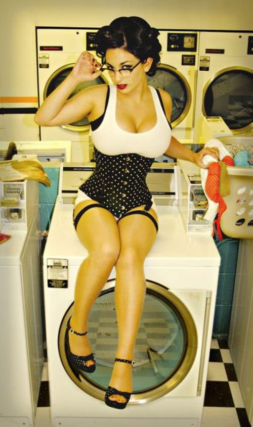 Pretty girl with glasses showing cleavage on a washing machine
